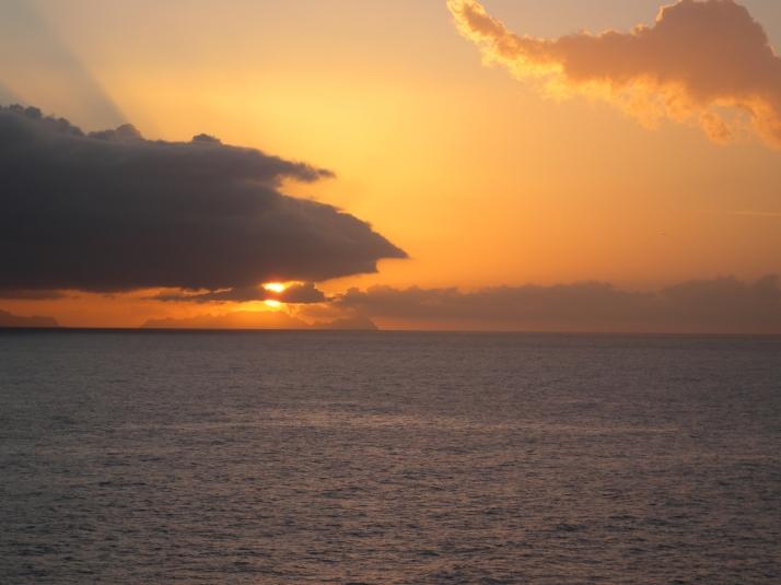 Kultainen aurinko työntyy esiin pilvien lomasta. Päivä nousee.