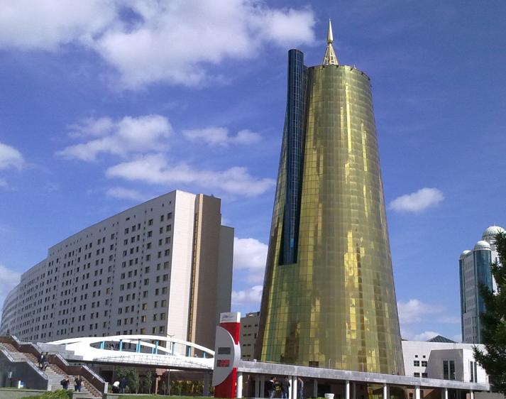 Kultainen siilomainen torni ja kaareva hallituksen rakennus, jossa valo taittuu ikkunoihin heijastaen kullan hohdetta. Astana.