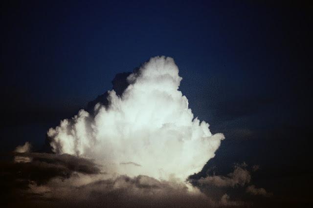 Valkoinen pilvi tummalla taivaalla.