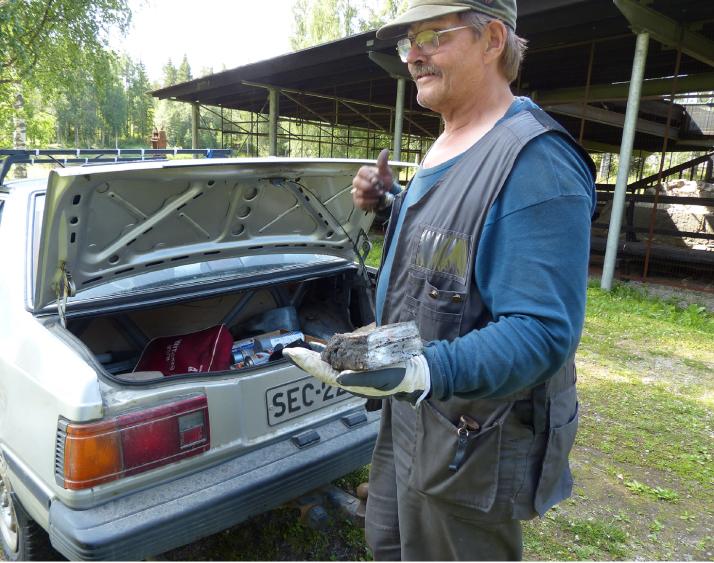 Urpo Parviainen esittelee takakontista esille kaivaamaansa materiaalia, josta hän takoo työkaluja ja koruja.