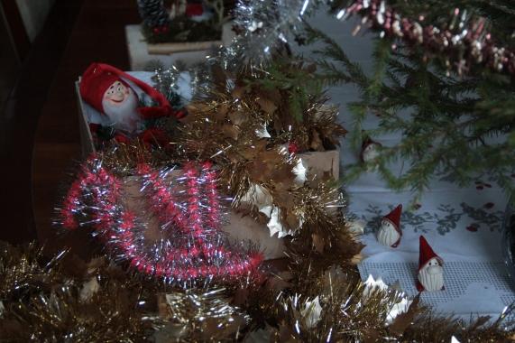 Joulun magiaa - kuusen koristeita, tonttuja ja kynttilöiden valoa kuusen oksan katveessa.