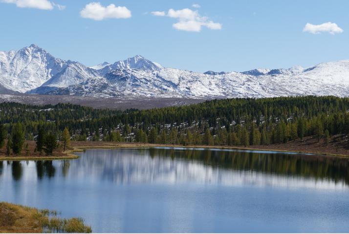 Vuoristojärven takana kohoavat lumiset huiput.