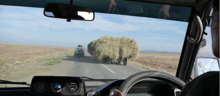 Auto ohittaa heinäkuormaa.